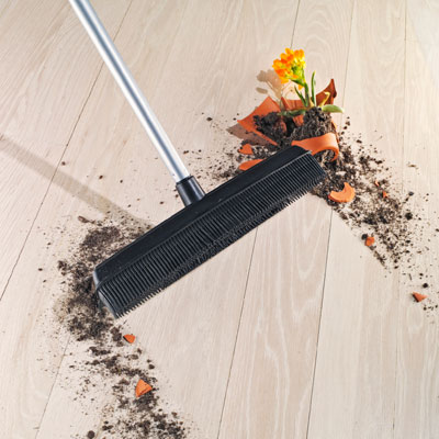 broom sweeping up mess of broken potted plant