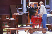 people browsing vintage furniture at flea market