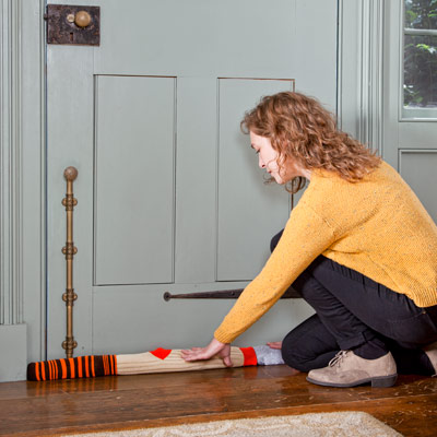 woman stuffing door jamb with old socks