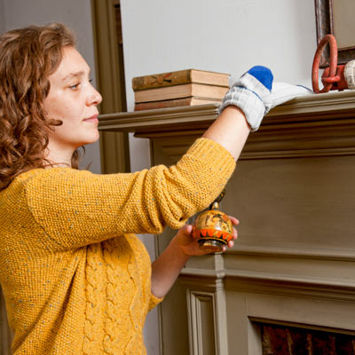 woman using old sock to dust mantel