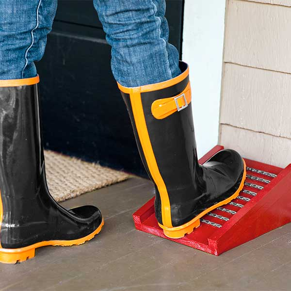 woman scraping her rain boots on boot scraper built with window sash chains