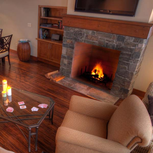 living room with fireplace, fire roaring and hardwood floors
