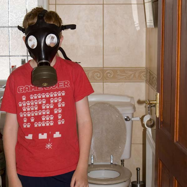 young boy with gas mask on in smelly bathroom