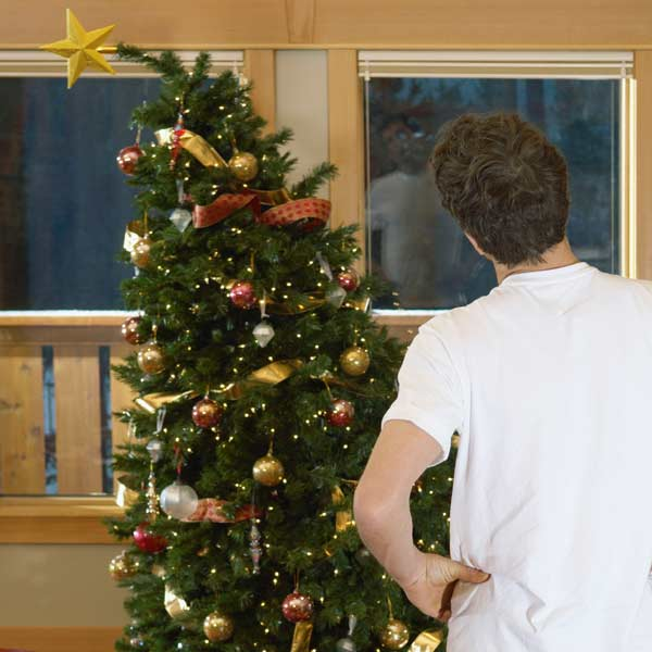 man looking at crooked Christmas tree
