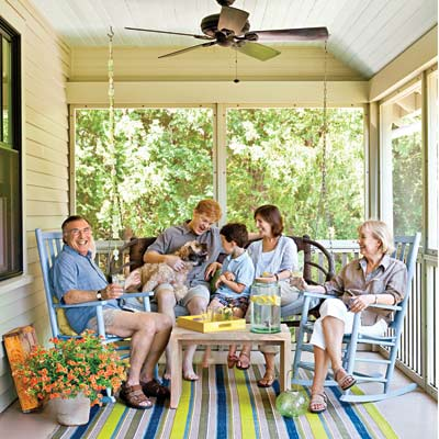 family sitting on porch swing, chairs on remodeled bungalow