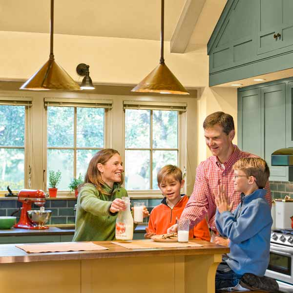 family gathered after whole-house renovation in kitchen with vaulted cathedral ceiling