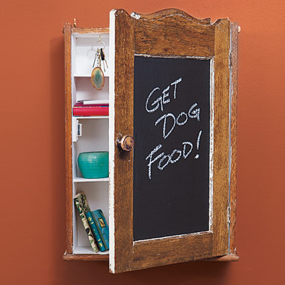 salvaged medicine cabinet made into a message center with storage inside and a chalkboard on front of door