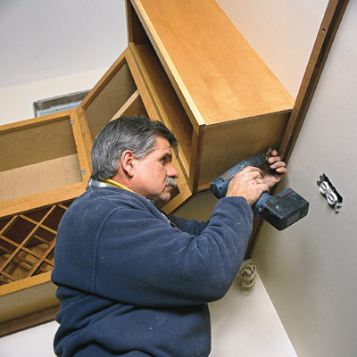 man hanging kitchen cabinets