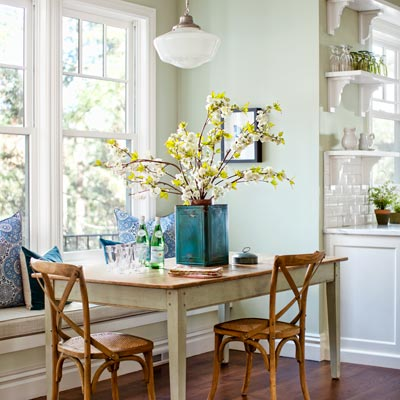 after kitchen remodel breakfast nook with schoolhouse pendant light, wood table, chairs and cushioned window seat 