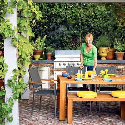 a woman sets the table at an outdoor kitchen/dining area