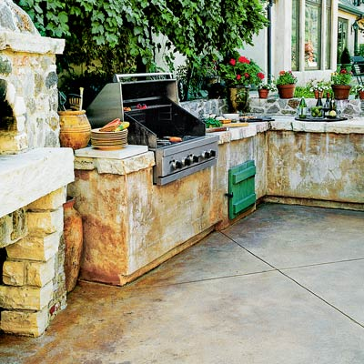 an outdoor kitchen with a rustic stucco look