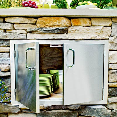 an outdoor kitchen island with stainless steel storage cabinet doors