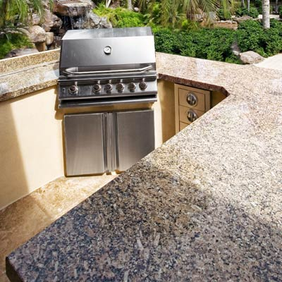 an outdoor kitchen with granite countertops