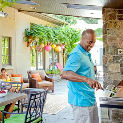man grilling with family seated nearby