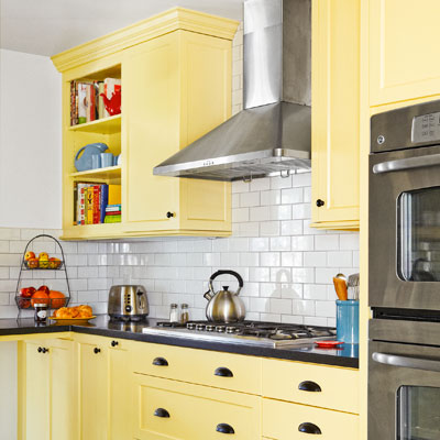 after kitchen redo yellow cabinets with solid-surface countertop mimic soapstone, white subway tile backsplash, yellow Shaker-style cabinets
