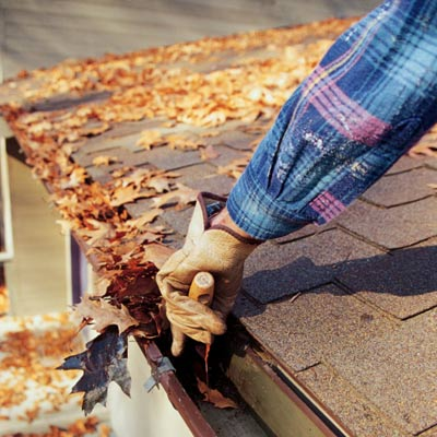 man cleaning leaves out of clogged gutters