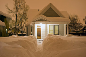 House at dusk after heavy snow storm with shoveled path
