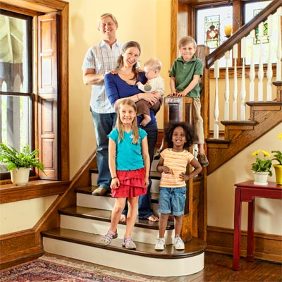 family gathered on staircase of the this old house reader remodel grand prize winning house