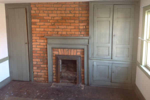Save This Old House West Newton, Pennsylvania interior mantel with exposed brick wall and built-in storage