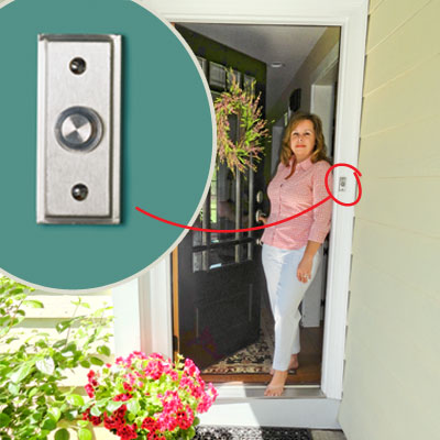 homeowner demonstrating how an new satin-finish doorbell compliments her handle and lockset