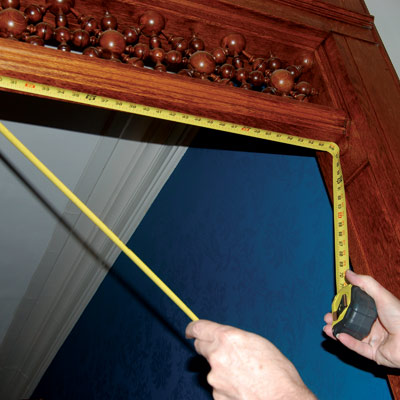 using tape measure to measure the top of a door frame