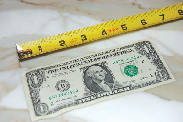 measuring tape measuring a dollar