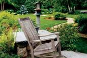 rocking chair on patio with backyard path in background
