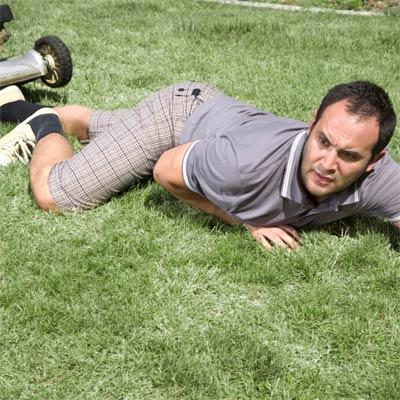 fallen man on lawn next to lawnmower