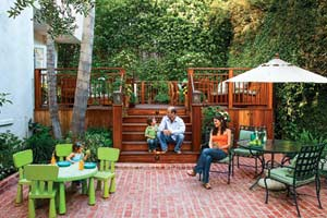 family on rebuilt backyard deck with brick patio