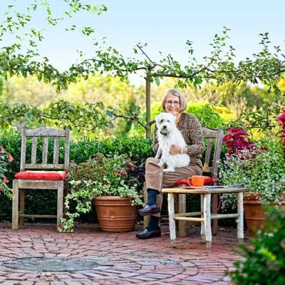 homeowner with dog on circular patio with pear and apple trees in autumn garden