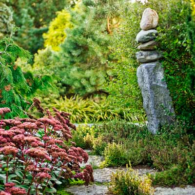 stone cairn beside pathway with Sedum 'Matrona', teucrium