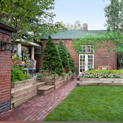 backyard brick path separates lawn and lounge from dining deck