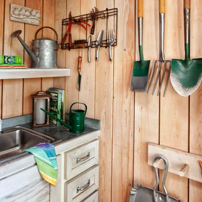 potting shed interior with redwood floor, pine plank walls, peg racks, galvanized-metal counters, stainless-steel trough sink