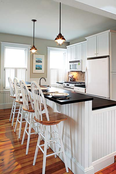 country style kitchen with black quartz kitchen countertops on white base bar with seats