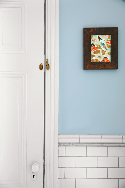 light blue master bath after remodel with white porcelain subway tile with marble pencil trim and chair rail cap