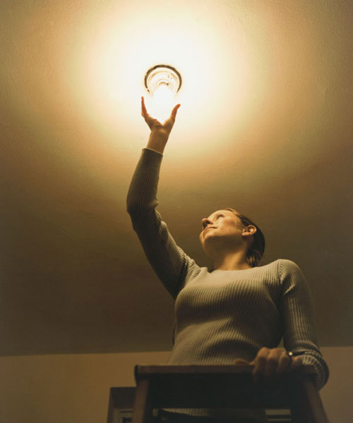 woman changing out light bulb in ceiling fixture, homeowner survival skills