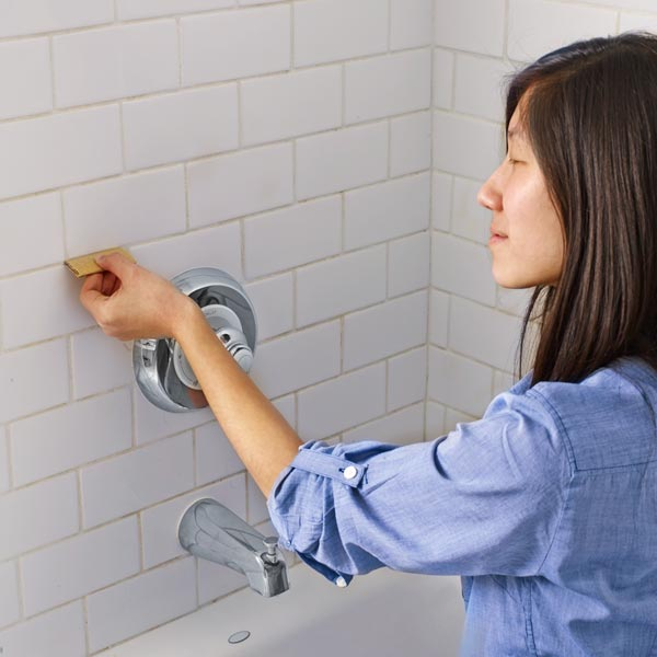 10 uses for sandpaper, woman cleaning up tile grout in shower