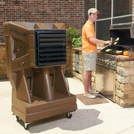 man grilling in outdoor kitchen with evaporative cooler nearby