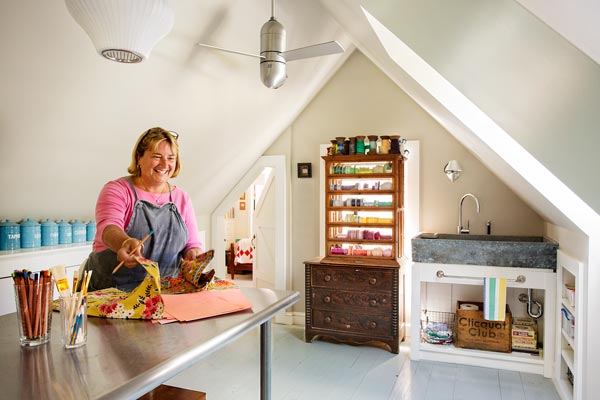 farmhouse whole house remodel homeowner in attic studio with built-in storage, salvaged soapstone sink