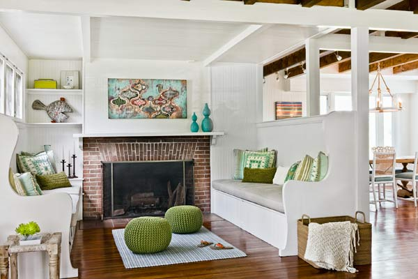 living area of 1910 shore house with dropped ceiling to hide electrical work, built-in benches, brick fireplace