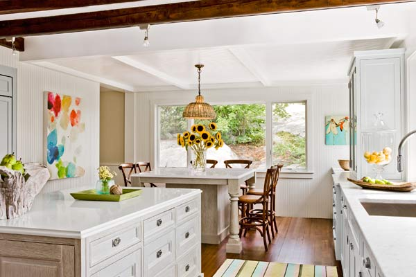 kitchen of 1910 shore house with exposed beam ceiling, white kitchen cabinets, kitchen island, beadboard walls