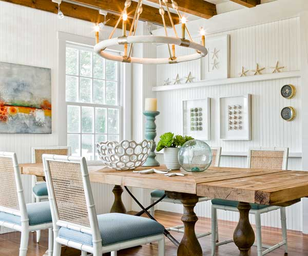 dining room of 1910 shore house with exposed beam ceiling, long dining table, heart pine floors, beadboard walls