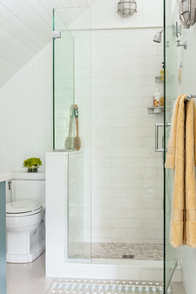 bath on third floor of 1910 shore house with frameless glass shower door, subway tile