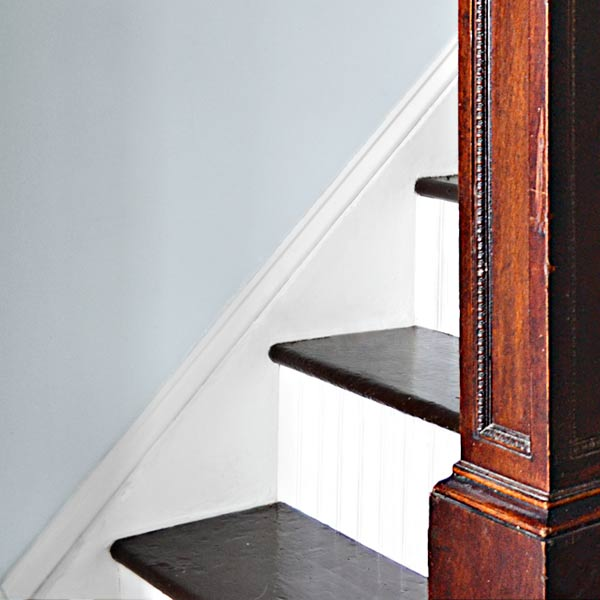 after remodel, close up of brown painted stair treads and white beadboard risers in foyer