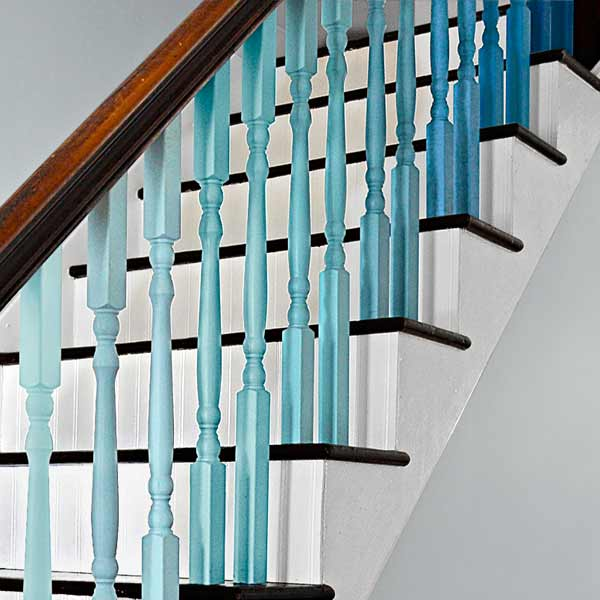 after remodel, close up of stair balusters painted blue ombre gradient