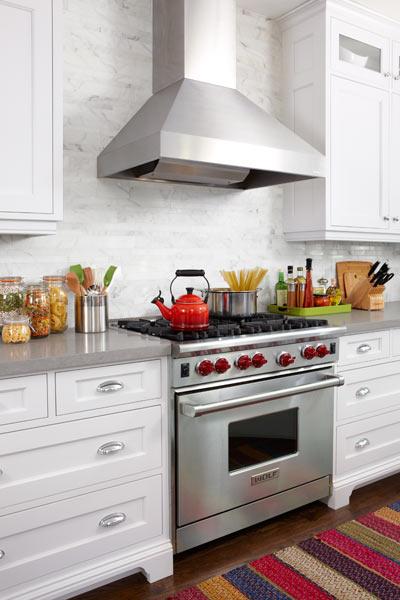 range with floating range hood against marble tile backsplash eat in kitchen after remodel