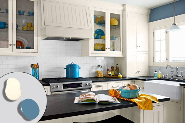 after remodel blue and white kitchen with white kitchen cabinets and crown molding, subway tile backsplash, kitchen island, beadboard range hood, pendant light, farmhouse sink