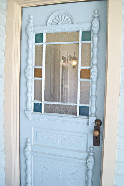 door with spindlework and original stained glass windows on light blue queen anne farmhouse garland texas save this old house