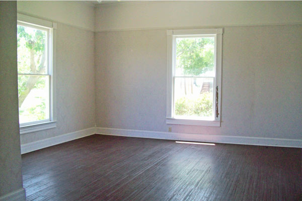 first floor room with tall ceilings, laminate floors, windows of light blue queen anne farmhouse garland texas save this old house