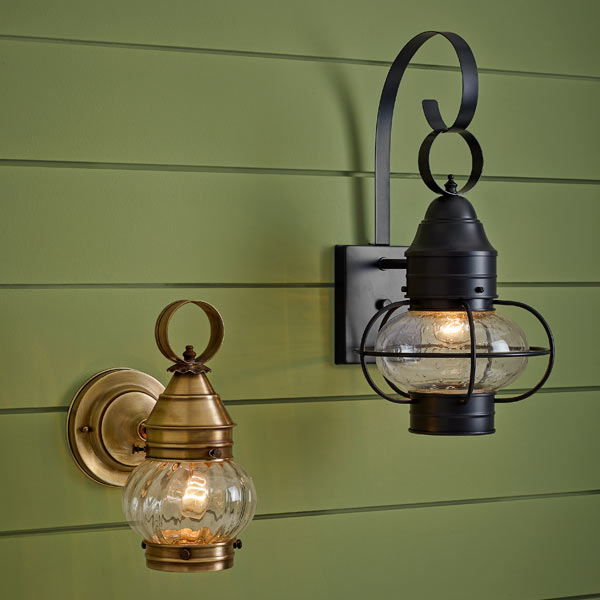 two onion-style porch lanterns mounted on green siding